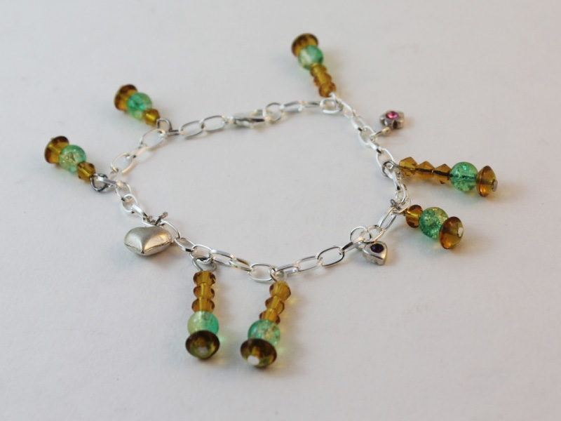 a completed charm bracelet featuring beaded and silver charms